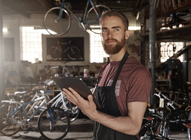 Using to modern technology to grow your dreams A young man in a bicycle repair shop standing with a digital tablet in his workshop bicycle shop stock pictures, royalty-free photos & images