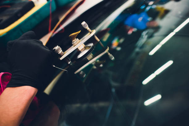 verwendung von werkzeugen, die repariert werden, um risswindschutzscheibe zu beheben - fensterbauer stock-fotos und bilder
