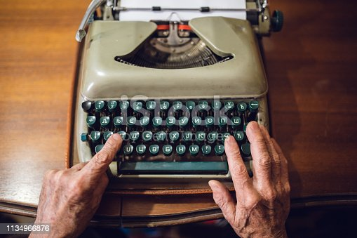Close-up of an elderly gentleman is using typewriter at his home