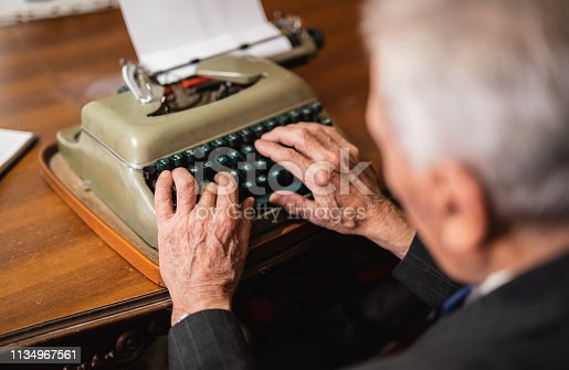 An elderly gentleman is using typewriter at his home
