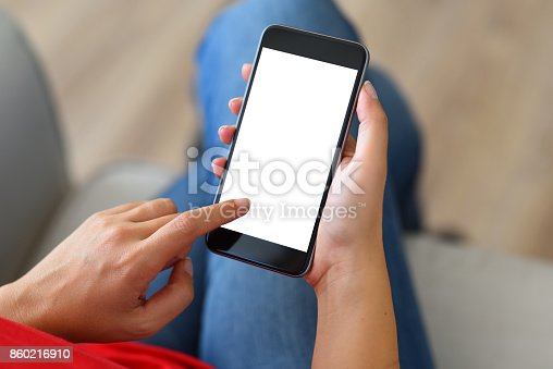 Woman using and touching a blank white screen smart phone on a couch.