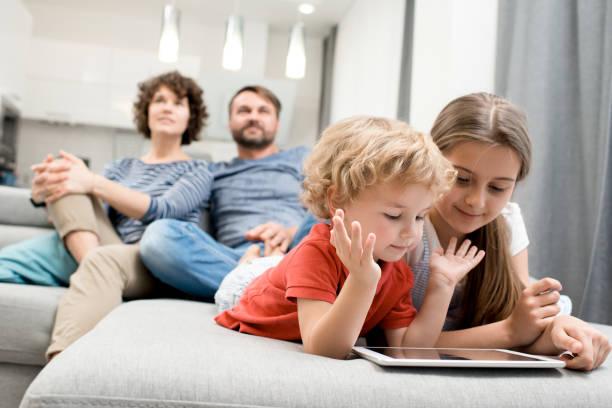 día habitual de familia encantadora - family watching tv fotografías e imágenes de stock