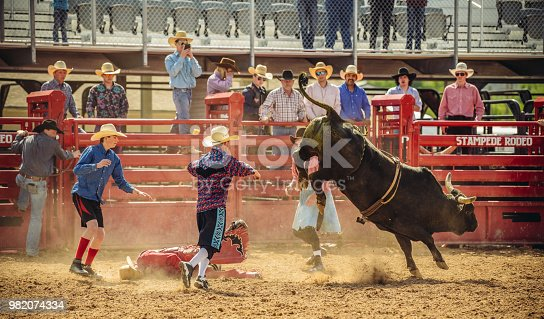 Bull riding rodeo in Utah, USA. Young cowboy riding a bull in the arena. Other cowboys looking over in the background, following the action.
