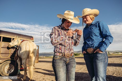 Two young women in cowgirl outfits looking at mobile phone, in the open field outside Salt Lake City, Utah.