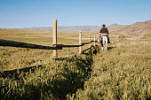 A rancher and his horse walk alongside a fence in rural Utah, USA.