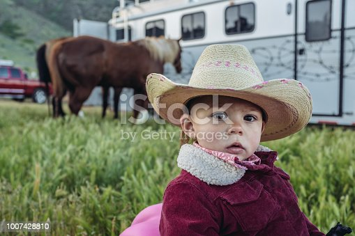 Portrait of a young Utah rancher, looking at camera. She is on the rocking horse, in the middle of  field with horses and trailer in the background..