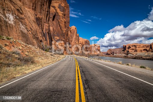 Colorful view from Utah Scenic Byway 279 with tall sandstone cliffs on one side and the Colorado river on the other, Moab, Utah