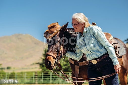 Senior cowgirl leading her horse in a coral. Outside Salt Lake City, Utah.