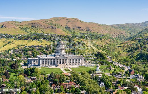 A high angle view of Utah's State Capitol building, flanked by mountains, in the north of Salt Lake City, Utah.