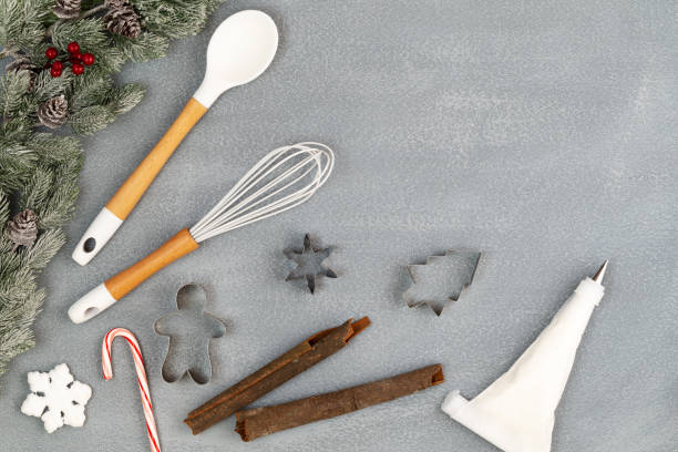 Utensils and spice for Christmas cooking or baking with spoon, whisk, icing piping bag, cookie cutters, cinnamon sticks, candy cane and snow flake with snowy fir branches over stone like background with copy space. Flat lay, top view. stock photo