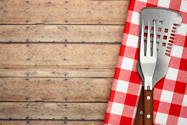 BBQ Utensils on Brown Rustic Picnic Table stock photo