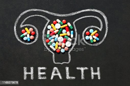 uterus and ovaries  with pills and word Health on blackboard