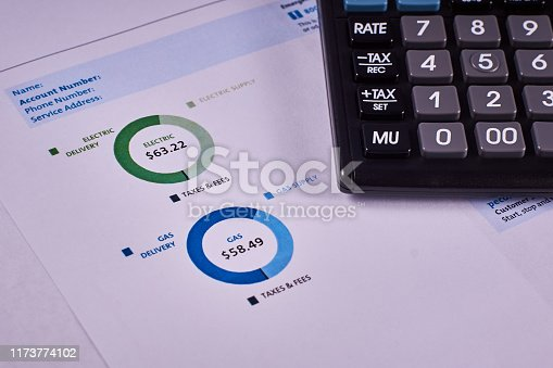 Communal payments. Pie charts gas and electric supply record in the utility bill next to calculator. Close-up