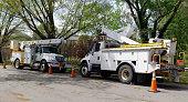 Parked telecommunications utility vehicle on shaded neighborhood street.