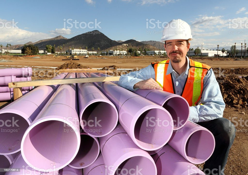 Utility Worker Leans on Stacked Purple Pipe royalty-free stock photo