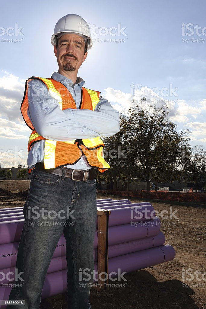 Utility Worker Stands Near Recycled Water Pipes royalty-free stock photo