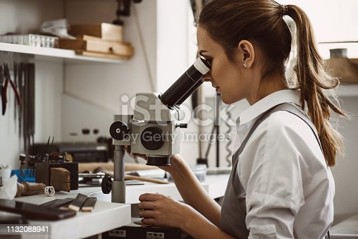 Utmost precision. Close up portrait of female jeweler looking at the new jewelery product through microscope in a workshop. Jewelry manufacturing concept. Jewelry making workshop. Master's hands