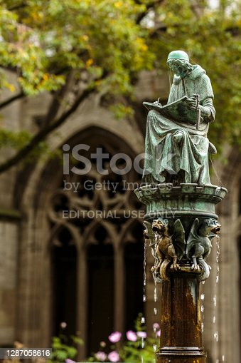 Utrecht, Netherlands - October 20, 2019: Courtyard of the Dom church at St. Martin's Cathedral, with fountain figure of Hugo Wstinc in Utrecht, Netherlands.