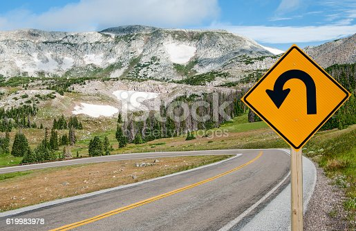 A sign warns motorists of a sharp bend ahead on a mountain road in southern Wyoming.