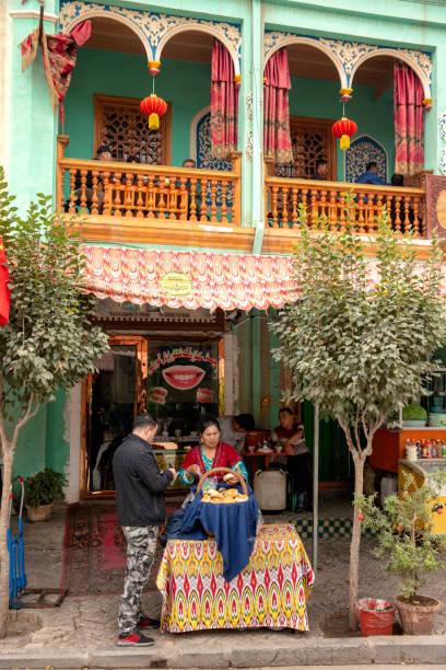 Uigurische Frau verkauft Nan Brot vor einem alten Teehaus in Kashgar. – Foto