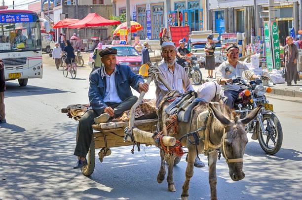 uigure leute sitzen am einkaufswagen ziehen mit esel - kuqa stock-fotos und bilder