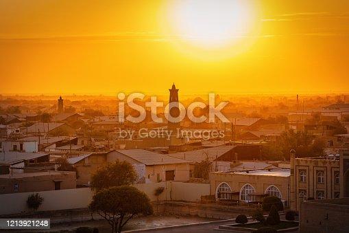Amazing sunset and twilight over the famous old city of Khiva - Xiva - Хива on the Silk Road with iconic islamic Islam Khoja Minaret in the center. Itchan Kala, Khiva - Chiva, Xorazm Region, Uzbekistan, Central Asia