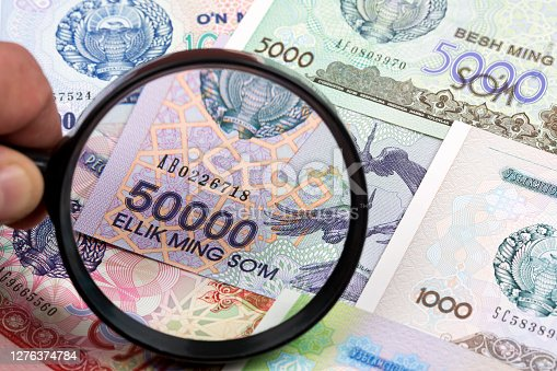 Uzbekistani money in a magnifying glass a business background
