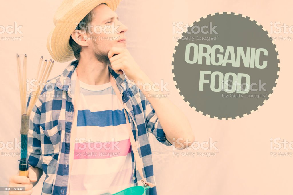 v young male farmer in casual shirt with fruit picker on isolated background with copy space concept stock photo