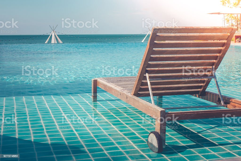 Vacation and Holiday Concept : Close up wooden daybed in swimming pool for sunbathing and resting in summer trip seasonal. Vacation and Holiday Concept : Close up wooden daybed in swimming pool for sunbathing and resting in summer trip seasonal. Beach Stock Photo