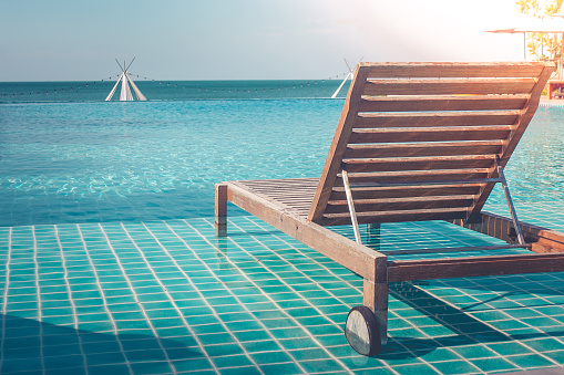 Vacation And Holiday Concept Close Up Wooden Daybed In Swimming Pool For Sunbathing And Resting In Summer Trip Seasonal Stock Photo - Download Image Now