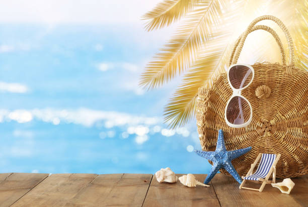 vacation and summer concept with sea life style objects over wooden table infront of sea landscape background – zdjęcie