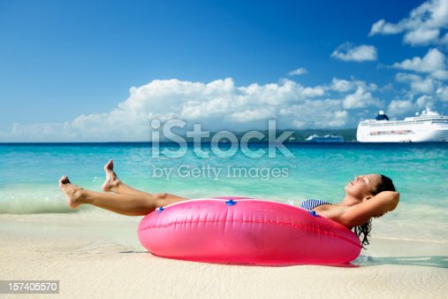 woman relaxing in raft on a beach with cruise ship in the background