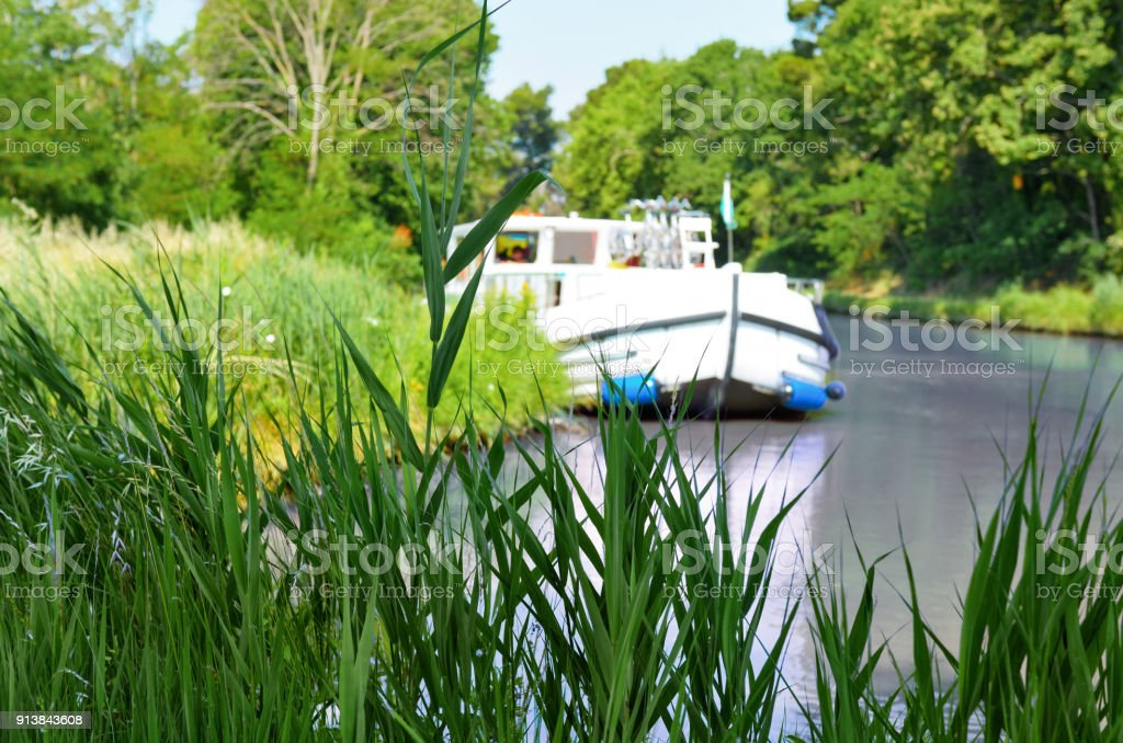 Vacation boat in Canal du Midi, family travel cruise by barge penichette, holidays in Southern France stock photo