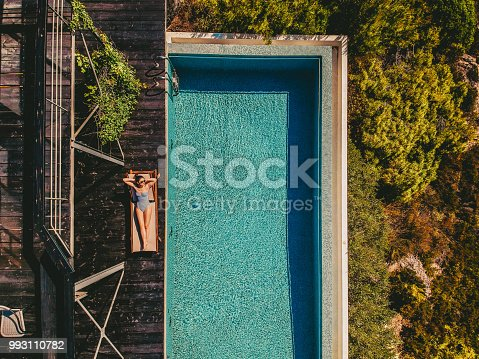 Aerial view of a young woman relaxing by the infinity pool