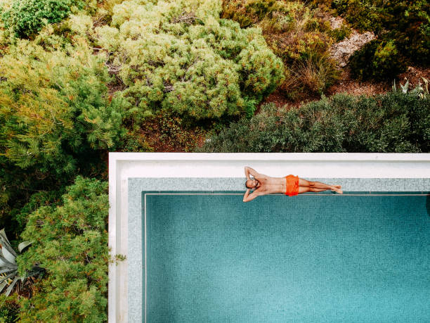 Vacation for one Aerial view of a young man relaxing by the infinity pool infinity pool stock pictures, royalty-free photos & images