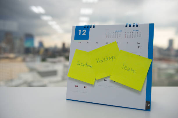Vacation, holiday and leave on paper note stick on the calendar of December for year end holidays concept stock photo