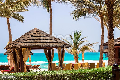 istock Vacation holidays background. Pavilion and sunbeds on ocean coast. 910108752