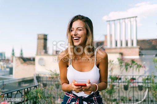 Smiling woman on rooftop terrace having fun in social media