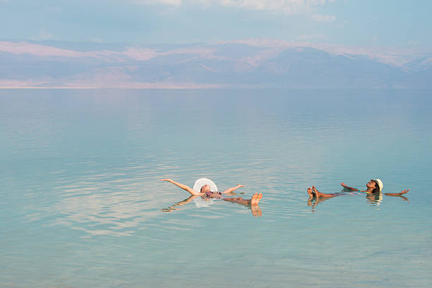 Vacation in Dead Sea with friends. Lovely multiracial girls wearing sun hats, lying on back with outstretched arms, floating in salty water of Dead Sea. Unusual buoyancy caused by high salinity. historical palestine stock pictures, royalty-free photos & images