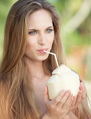 Beautiful Woman with beautiful natural long hair holding a Coconut Drink at the Beach. Converted from RAW. Nikon D800e.