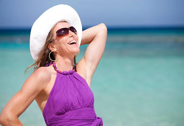 Vacation Lifestyles-Beautiful Woman Laughing at Beach stock photo