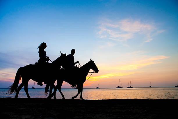 Vacation Lifestyles-Couple Horseback Riding at Sunset stock photo