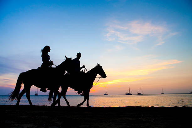 Urlaubsgefühl-Paar Reiten bei Sonnenuntergang – Foto