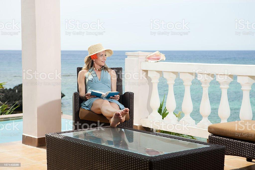 Vacation Lifestyles-Woman Reading on Balcony royalty-free stock photo