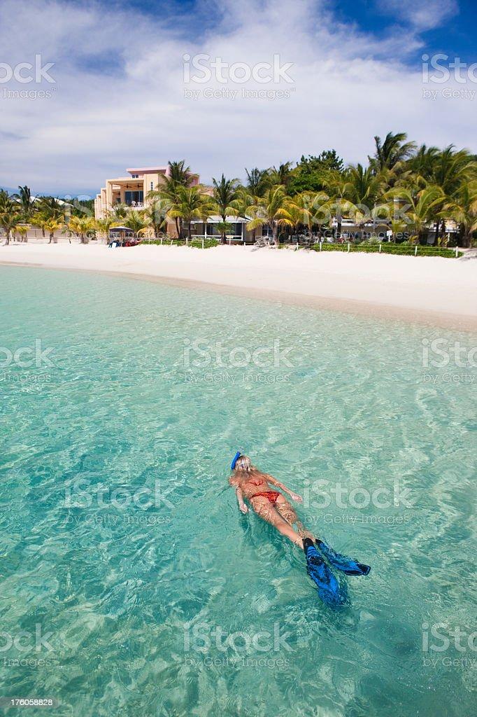 Vacation Lifestyles-Woman Snorkeling Near Tropical Beach stock photo
