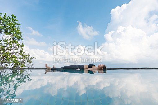 istock Vacation of Beautiful Attractive Asian woman relaxing in yoga Savasana pose on the pool above the beach with beautiful sea in Tropical island,Feeling comfortable and relax in holiday,Vacations Concept 1152223612