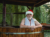 Senior man as Santa Claus with towel standing in a bath with warm water outside and looking with smiling at the camera.