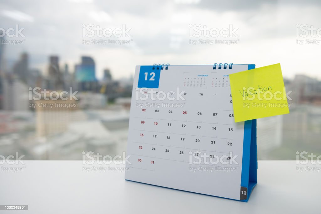 Vacation on paper note stick on the calendar of December for year end holidays concept stock photo