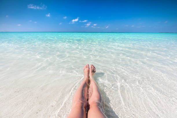 Vacation on tropical beach in Maldives. Woman's legs in the clear ocean stock photo