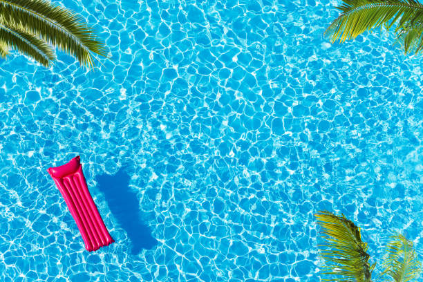 Vacation pool with matrass surface and palm trees Vacation pool hotel view from above with ping matrass floating, water surface and palm trees swimming pool stock pictures, royalty-free photos & images